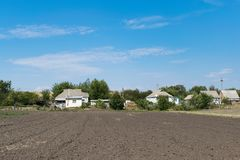 Tillage in the country. Tillage on the land near the village house Stock Photography