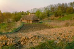 Tillage goes to old wooden house. Rural landscape in the morning Royalty Free Stock Photo