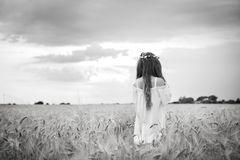 Tillbaka av en härlig flicka i ett vetefält med långt hår och en krans royaltyfri fotografi