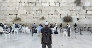 Tillbaka av en ung turist i tillfällig kläder och kippah på huvudet som ser den att jämra sig väggen och klosterbrodern som ber n royaltyfri fotografi