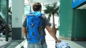Tillbaka av sikten av den unga mannen med ryggsäcken som drar resväskan i modern flygplatsterminal Resa stiligt gå för grabb royaltyfri bild