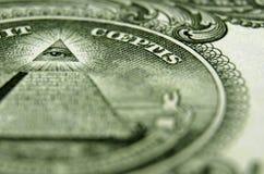 Tillbaka av US dollarräkningen, fokuserat på ögat ovanför pyramiden royaltyfria foton