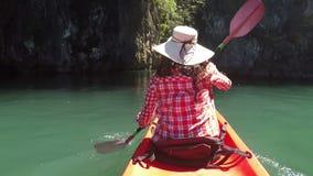 Tillbaka bakre sikt av kvinnan som kayaking i den härliga lagunhandlingkameran pov av flickan som paddlar på kajakfartyget stock video