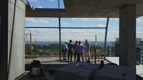Tillbaka bakre sikt för antenn av gruppen av byggmästare på konstruktionsplats, teknikerer på byggnadsobjekt som diskuterar plan  stock video