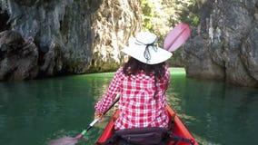 Tillbaka baksida av kvinnan som kayaking i den härliga sikten för lagunhandlingkamera av flickan som paddlar på kajakfartyget arkivfilmer