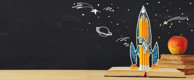tillbaka banerskola till raket skissar och blyertspennor över den öppna boken framme av klassrumsvart tavla royaltyfri fotografi