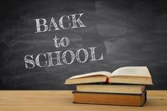 tillbaka begreppsskola till bunt av böcker över träskrivbordet framme av svart tavla royaltyfria foton