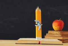 tillbaka begreppsskola till bunt av böcker och blyertspennor över träskrivbordet framme av svart tavla arkivfoton