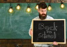 tillbaka begreppsskola till Lärare i glasögon som rymmer den svart tavlan med sats tillbaka till skolan skriftlig i den 308 mässi Royaltyfri Fotografi