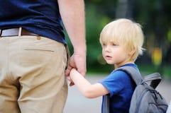 tillbaka begreppsskola till Liten elev med hans fader Första dag av grundskola för barn mellan 5 och 11 år royaltyfria bilder