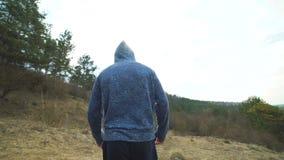 Tillbaka blick av mannen som går på gräsmattan för skog` s långsamt arkivfilmer