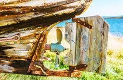 Tillbaka del av den ljusa gamla övergav fiskebåten på kusten royaltyfri bild