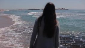 Tillbaka i halvfigur sikt av en flicka med länge löst mörkt hår som går i vatten på stranden långsam rörelse lager videofilmer