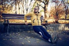 Tillbaka liggande armhävningar på parkerar bänken man som fungerar ut Fotografering för Bildbyråer