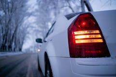 Tillbaka ljus av den uppochnervända sikten för vit bil Vinter Arkivbild