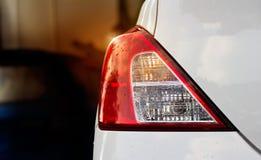 Tillbaka ljus av den vita bilen efter regnet på bilparkering arkivfoto