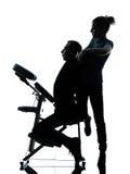 Tillbaka massageterapi med stolkonturn Arkivfoto