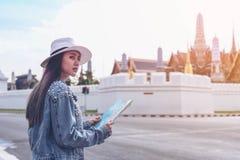 Tillbaka packare för unga handelsresandekvinnor som bara reser i stadsscape i Thailand, storslagen slott som en suddig bakgrund royaltyfri bild