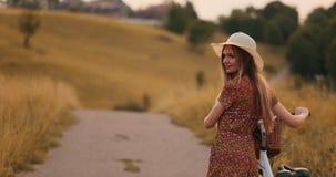 Tillbaka plan: härlig blondin i klänning och retro cykel som går på vägen i sommarfältet lager videofilmer