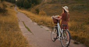 Tillbaka plan: härlig blondin i klänning och retro cykel som går på vägen i sommarfältet stock video