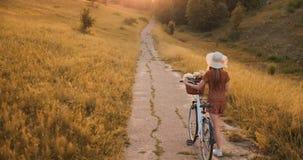 Tillbaka plan: Härlig blondin i klänning och retro cykel som går på vägen i sommarfältet arkivfilmer