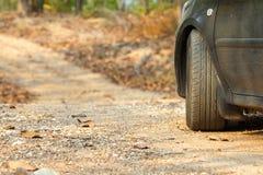 Tillbaka sida av bilparkering på den grusväg/mountain vägen/landsvägen i skog i Thailand Arkivbilder