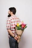 Tillbaka sida av den stiliga unga mannen med skägget och trevlig bukett av blommor Arkivfoto