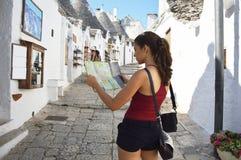 Tillbaka sida av handelsresandeflickan som söker rätt riktning på översikt BesökAlberobello för ung kvinna trulli i den Apulia re royaltyfria foton