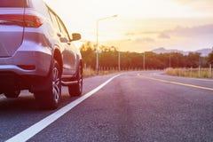 Tillbaka sida av ny parkering för silverSUV bil på asfaltvägen Royaltyfri Fotografi