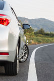 Tillbaka sida av ny silverbilparkering på asfaltvägen Arkivbild