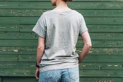 tillbaka sikt Är den iklädda gråa t-skjortan för den unga millennial kvinnan ställningar mot den gröna wood väggen Arkivbilder