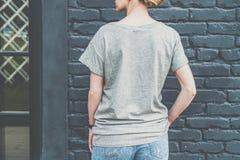 tillbaka sikt Är den iklädda gråa t-skjortan för den unga millennial kvinnan ställningar mot den mörka tegelstenväggen Royaltyfri Fotografi