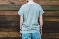 tillbaka sikt Är den iklädda gråa t-skjortan för den unga millennial kvinnan ställningar mot den mörka wood väggen Arkivfoton