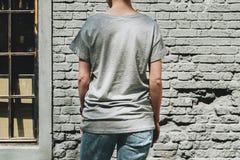 tillbaka sikt Är den iklädda gråa t-skjortan för den unga millennial kvinnan ställningar mot den gråa tegelstenväggen Arkivfoto