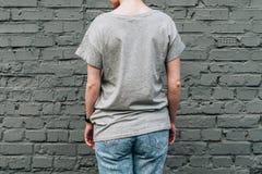 tillbaka sikt Är den iklädda gråa t-skjortan för den unga millennial kvinnan ställningar mot den gråa tegelstenväggen Arkivbild