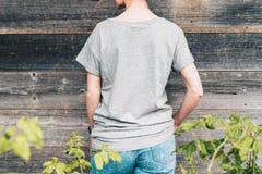 tillbaka sikt Är den iklädda gråa t-skjortan för den unga millennial kvinnan ställningar mot den gråa wood väggen Royaltyfri Foto