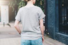tillbaka sikt Är den iklädda gråa t-skjortan för den unga millennial kvinnan ställningar på stadsgatan Åtlöje upp Arkivbild