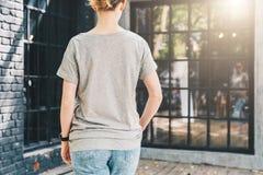 tillbaka sikt Är den iklädda gråa t-skjortan för den unga millennial kvinnan ställningar på stadsgatan Åtlöje upp Royaltyfria Bilder