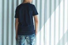 tillbaka sikt Är den iklädda svarta t-skjortan för den unga hipsterpojken ställningar inomhus mot den vita väggen Åtlöje upp Utry Royaltyfria Foton