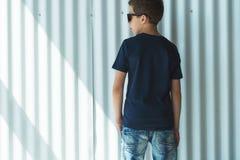 tillbaka sikt Är den iklädda svarta t-skjortan för den unga hipsterpojken ställningar inomhus mot den vita väggen Åtlöje upp Utry Royaltyfri Foto