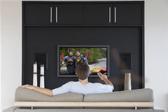 Tillbaka sikt av ändrande kanaler för mitt--vuxen människa man med televisionfjärrkontroll i vardagsrum royaltyfria bilder