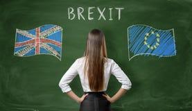 Tillbaka sikt av affärskvinnaanseendet på svart tavla med UK- och EU-flaggor Royaltyfri Foto