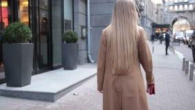 Tillbaka sikt av affärskvinnan som går på stadsgatan arkivfilmer