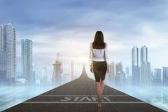 Tillbaka sikt av affärskvinnan som går till pilen Arkivbilder