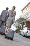 Tillbaka sikt av affärspar som går med bagage på körbanan Arkivfoton