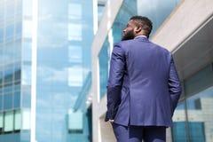 Tillbaka sikt av afrikansk amerikanaffärsmannen som utomhus promenerar stora kontorsfönster Skott fr?n baksida close upp arkivbilder