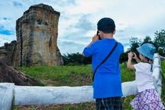 Tillbaka sikt av asiatiska barn som tar foto vid kameran Arkivbilder