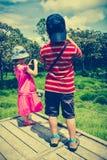 Tillbaka sikt av asiatiska barn som utomhus kopplar av i dagen, tr Royaltyfri Foto