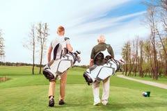 Tillbaka sikt av att gå golfspelare på kurs Arkivfoto