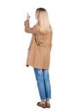 Tillbaka sikt av att peka den bruna kappan för womanin Arkivbild
